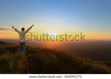 Tourist man spread hand on top of a mountain enjoying valley sunset view.