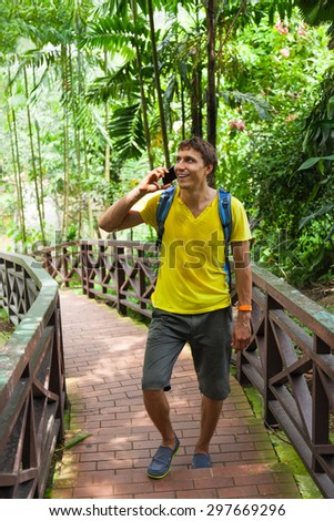 Tourist man using cell smart phone call smile summer vacation green tree asia park travel communication