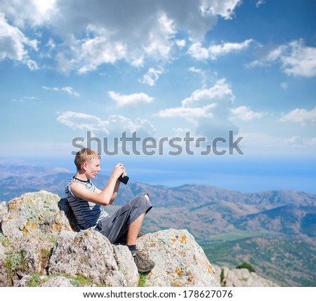 tourist on top of a mountain takes a snapshot of the nature