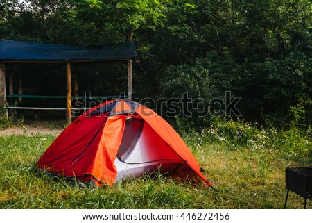 Tourist orange tent in forest at campsite. Camping place in the meadow on nature in summer. Adventure travel active lifestyle outdoor background. Family time holidays. - stock photo