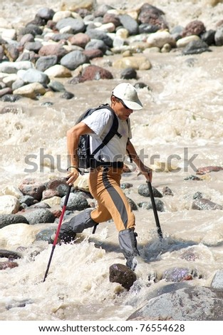 Tourist passes turbulent river. Risk and danger - stock photo
