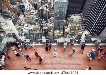 Tourist people taking pictures from rooftop on Manhattan skyscraper - stock photo