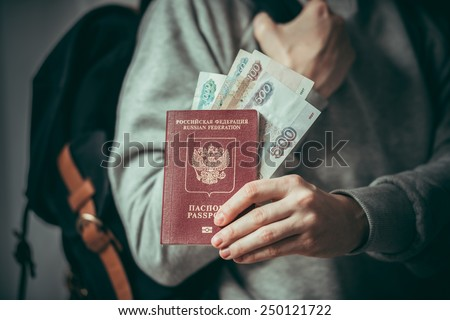 Tourist person holds russian passport and russian rouble bills. Toned picture - stock photo