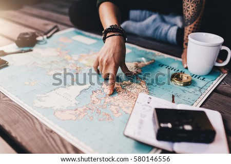 Tourist planning vacation with the help of world map with other travel accessories around. Young woman pointing at North America on the world map.
