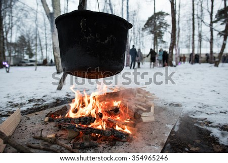 Tourist pot hanging over the fire in the forest in winter, cooking over a campfire - stock photo