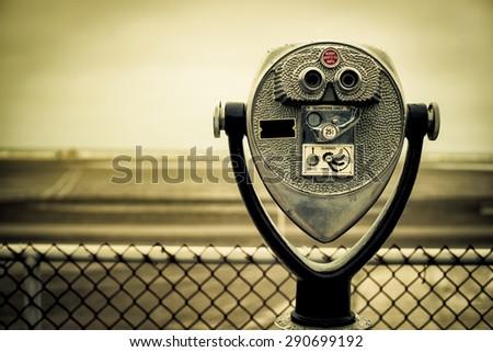 tourist retro coin operated binoculars on the beach - stock photo