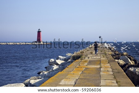 Tourist running on the pier and scaring the birds away. - stock photo