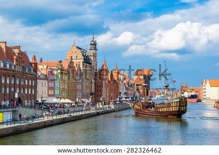 Tourist ship and colourful historic houses reflection Motlawa river in port of Gdansk, Baltic Sea, Poland. - stock photo
