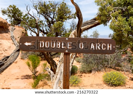 tourist sign showing the direction of hiking path towards Double O Arch in Utah  - stock photo