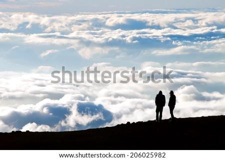 Tourist silhouette watching sunset on the top of  Haleakala volcano on Maui Hawaii - stock photo