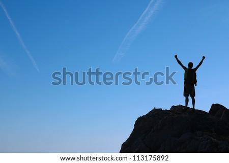 Tourist Silhouettes of tourists on a mountain top - stock photo