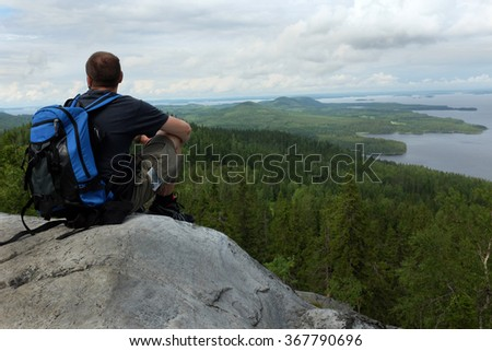 tourist sits on a high cliff in the national park Koli, Finland - stock photo