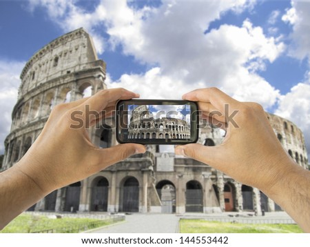 tourist takes a picture with his mobile of coliseum in Rome in Italy - stock photo