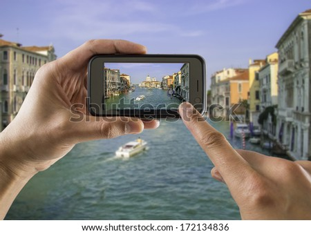 tourist takes a picture with his mobile of the  grand canal and basilica santa Maria della salute in venice - stock photo