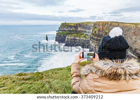 Tourist taking a photo with smartphone about Cliffs of Moher - stock photo
