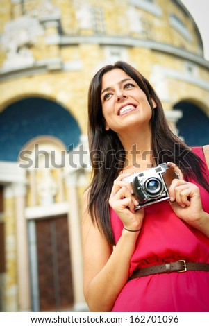 Tourist taking pictures with retro camera while traveling in Europe. Happy tourist taking pictures. - stock photo