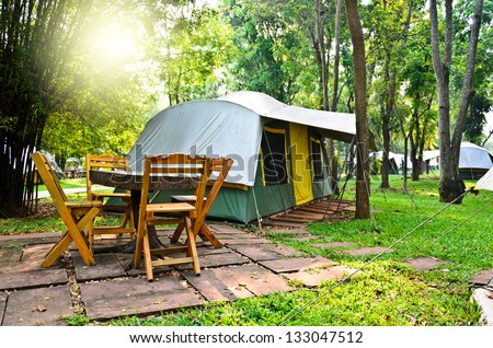 tourist tent in forest camp with sun rise - stock photo