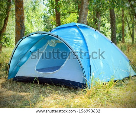 Tourist tent in the green fores - stock photo