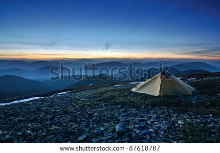 Tourist tent in the rocky mountains and first star on the horizon - stock photo
