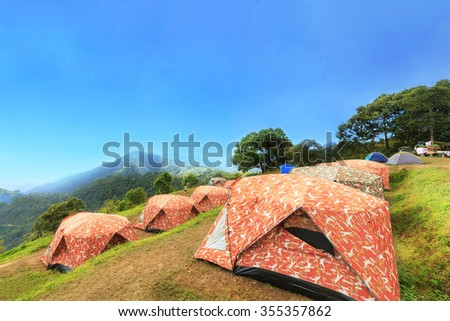 Tourist tents in camp among meadow on the mountain. - stock photo