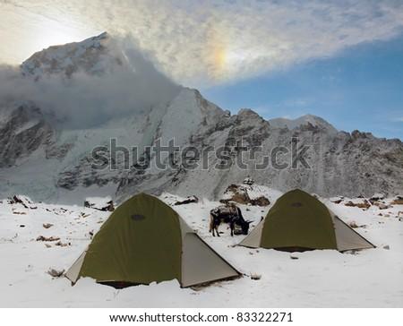 Tourist tents in Gorak Shep against sun halo, Nepal - stock photo