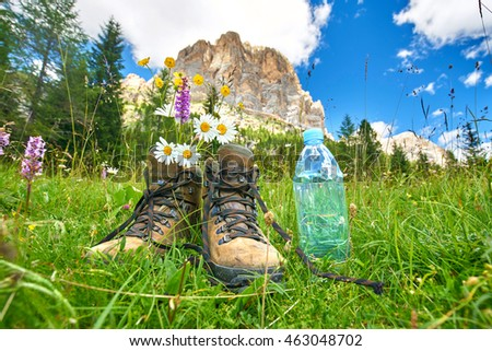 tourist traveler hiker shoes boots with fresh water standing on a trail in the mountains