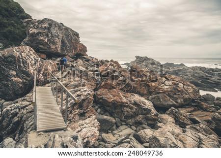 Tourist walking along the wild coast of Tsitsikamma National Park. Eastern Cape. South Africa. - stock photo