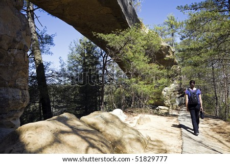 Tourist walking by the natural bridge in Red River Gorge State Park, Kentucky. - stock photo
