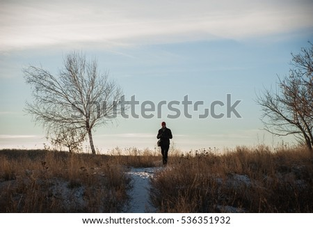 Tourist walking on the hill in winter. A tourist photographs the panorama of Saratov. A man out for a walk in the winter.