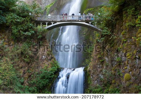 Tourist walking over Multnomah Falls - stock photo