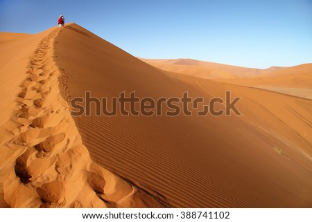 Tourist walking up a dune in Sossusvlei, Namib Naukluft National Park, Namib desert, Namibia. - stock photo