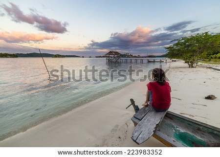 Tourist watching a relaxing sunset sitting on the beach, Togean Islands, Central Sulawesi, Indonesia. - stock photo