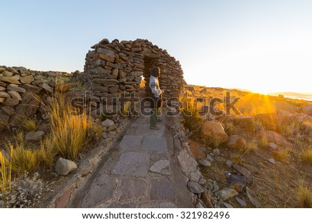 Tourist watching the sunset on Amantani' Island, Titicaca Lake, among the most scenic travel destination in Peru. Travel adventures and vacations in the Americas. Wide angle view in backlight. - stock photo
