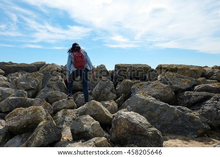 Tourist wear jean jacket and shouldered a red rucksack , climb on rocky coastline with blue sky , success concept - stock photo