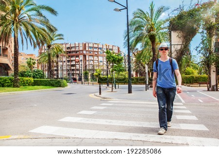 Tourist with a backpack crossing the road in Valencia, Spain - stock photo