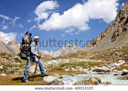 Tourist with a backpack in a mountain valley - stock photo