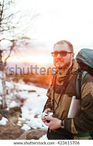 tourist with a camera on a background of a winter landscape in the mountains - stock photo