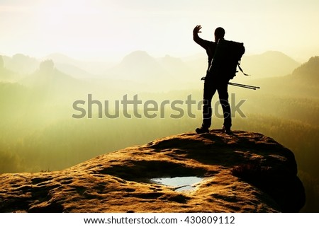 Tourist with backpack and poles in hand shadowing eyes. Sunny spring daybreak in rocky mountains. Hiker on rocky view point above misty valley.