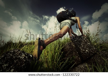 Tourist with backpack climbing a steep rock - stock photo