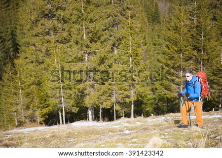 Tourist with backpack is traveling along a trail in the woods. - stock photo