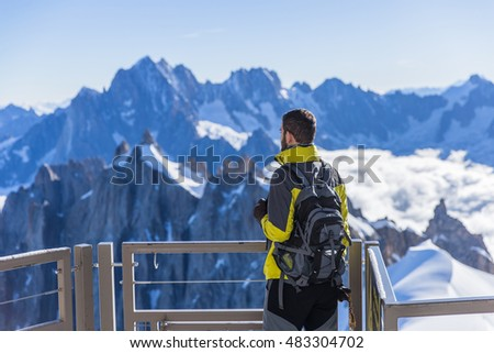 Tourist with backpack looks at the mountains in French Alps