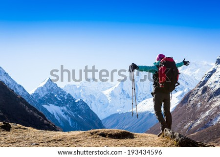 Tourist with backpack standing on a rock on clear sky background