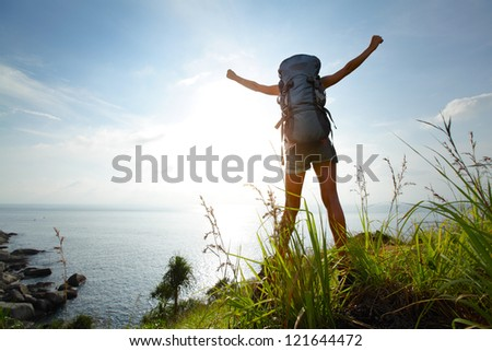 Tourist with backpack standing on sea coast with raised hands - stock photo