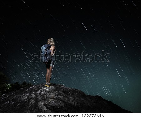 Tourist with backpack standing on top of a mountain and enjoying night sky view with stars - stock photo