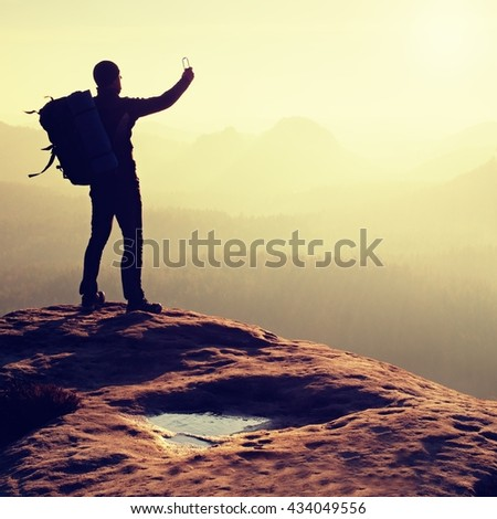 Tourist with backpack takes photos with smart phone on the rocky peak. Dreamy fogy valley below - stock photo
