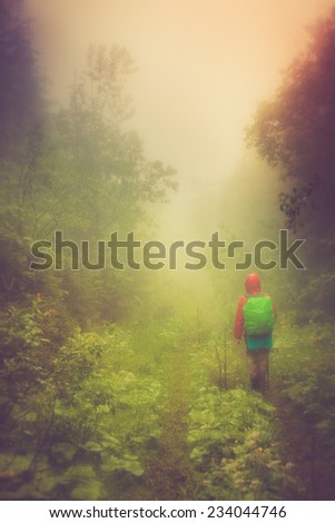 Tourist with backpack walking along on the road in fog in mountains. Filtered image: Soft and vintage effects.  - stock photo