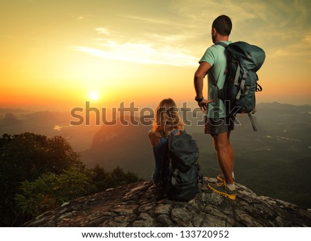 Tourist with backpacks enjoying sunrise on top of a mountain - stock photo