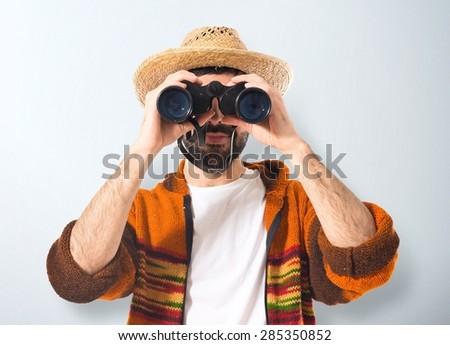 Tourist with binoculars over textured background - stock photo