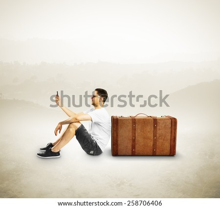 tourist with cellphone sitting near travel bag - stock photo