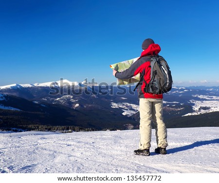 Tourist with map in the mountain valley. Sport and active - stock photo